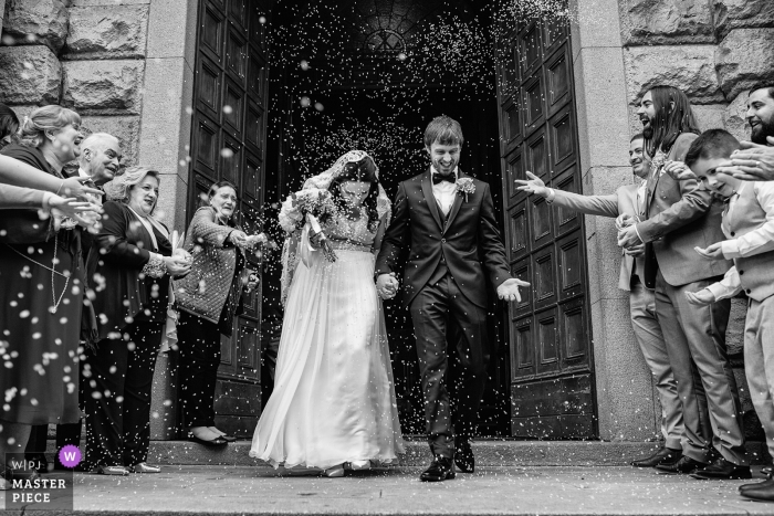 Black and white photo of the bride and groom emerging from the Villa Molin as guests throw rice by a Veneto, Italy wedding photographer.