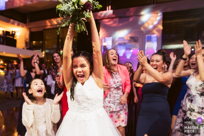 Curzon Hall, Sydney wedding photography - Young Girl steals the bouquet before the other women and celebrates