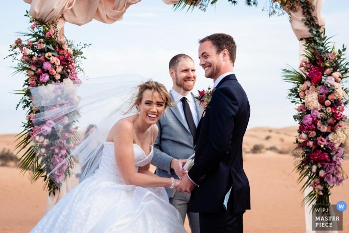 Al Maha Desert Resort Dubai Outdoor Ceremony in the Sand - Photo of the Brides reaction to the grooms joke