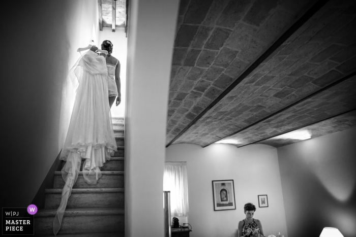 Black and white photo of a woman carrying the bride's wedding gown upstairs over her shoulder in Marche by an Italy wedding photographer.