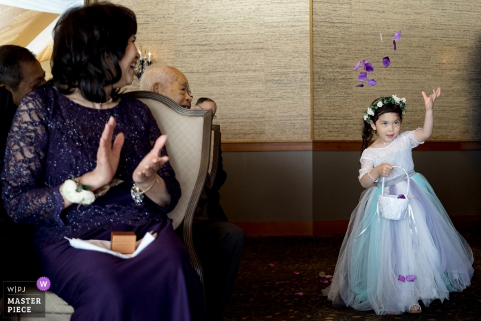 Edgewater Hotel wedding photograph of the Flower girl throwing flower pedals in the air during wedding ceremony