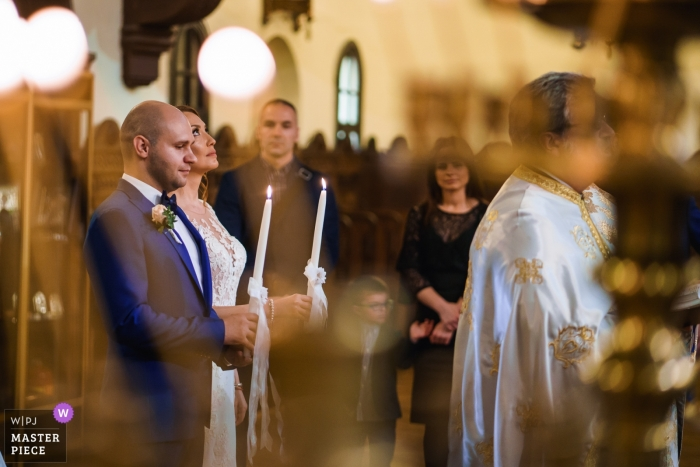 Sofia, St. Nedelia church photography - The ceremony with the bride and groom holding candles with her eyes fixed upwards.