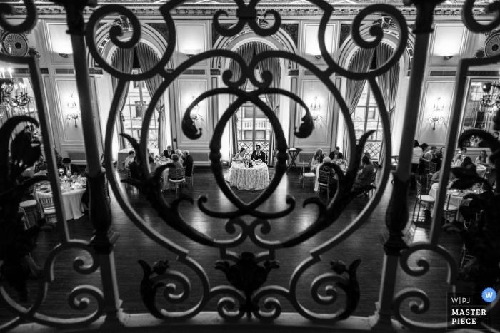 Colony Club, Detroit, MI - Bild durch die schmiedeeisernen Baluster des Sweetheart-Tisches während des Empfangs
