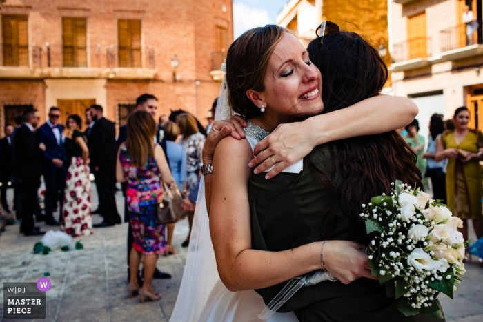 A photo of the bride hugging her friend was captured by a Valencia wedding photographer