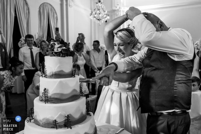 LA8, Baden-Baden Hochzeitsfoto der Braut und des Bräutigams Kämpfe, um die Kontrolle zu bekommen, um den Kuchen zu schneiden