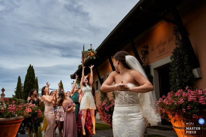 """Antica Fattoria di Paterno - Tuscany classic wedding photo of """"throwing the bouquet"""""""