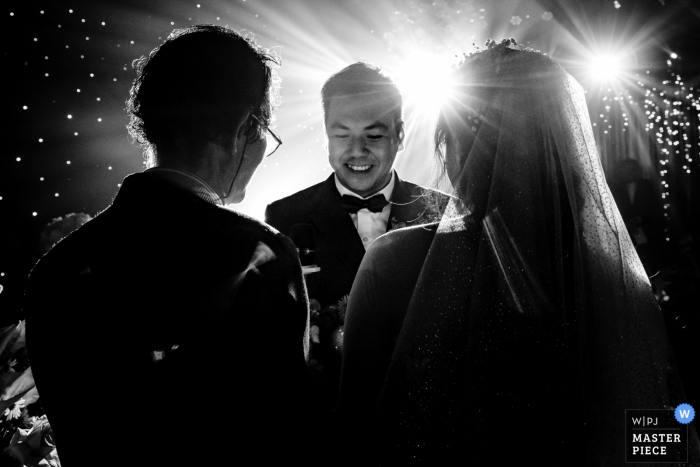 This black and white photo of the bride and groom saying their vows as bright spotlights shine behind was captured by a 	Ho Chi Minh wedding photographer