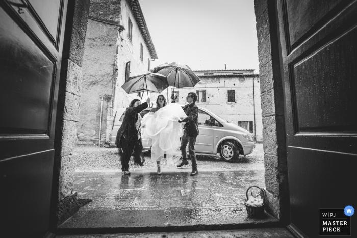 Abbadia Isola, Monteriggioni, Siena huwelijksfoto die de aankomst van de bruid onder de regen tonen