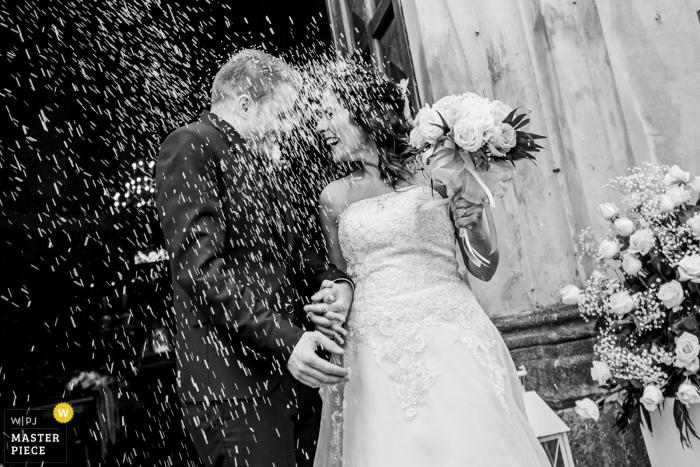 Lecco-trouwfotograaf heeft deze zwart-witfoto gemaakt van de bruid en bruidegom die met hun confetti bij hun ceremonie aan het Comomeer regenden
