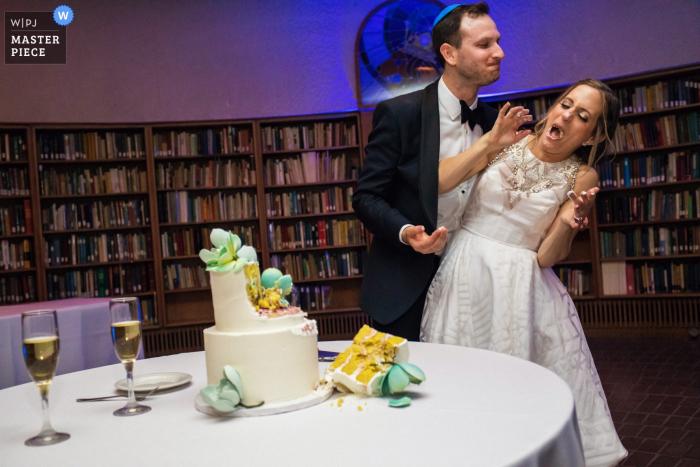 Foto dello sposo e della sposa che si godono il momento subito dopo il taglio della torta e si alimentano aggressivamente a vicenda presso l'American Jewish University-Brandeis Bardin Campus, Brandeis, CA