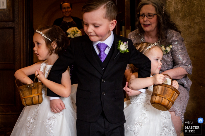 Edmonton wedding photography showing ring bearer helping flowergirls down the aisle