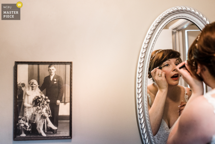 New West, BC wedding photography showing the bride touching up makeup with grandparents wedding photo next to her.