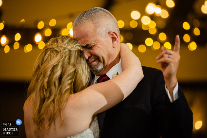 The Ballroom at Ellis Preserve Wedding Photography capturing the Dad dancing with his daughter. Getting emotional and pointing up to the sky for his recent loss of his mom.