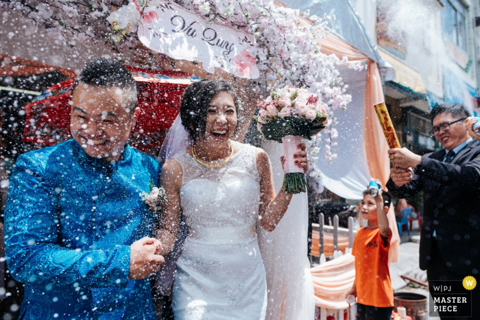 This photo of the bride and groom being showered with confetti after their ceremony was captured by a Ho Chi Minh wedding photographer