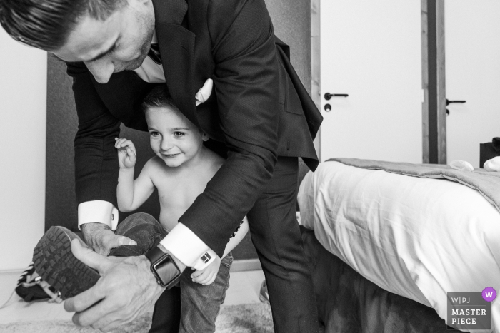 Wedding photo of preparations in a small room with a kid at the Chateau de Chapeau Cornu