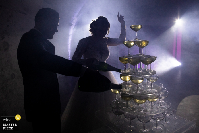 Chateau de Chapeau Cornu Wedding Reception Champagne time! | Photo of the bride and groom pouring from the bottles into a tower of glasses.
