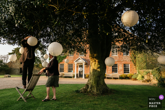 Westenhanger Castle, Kent wedding photograph showing a man putting up Lantern in a tree