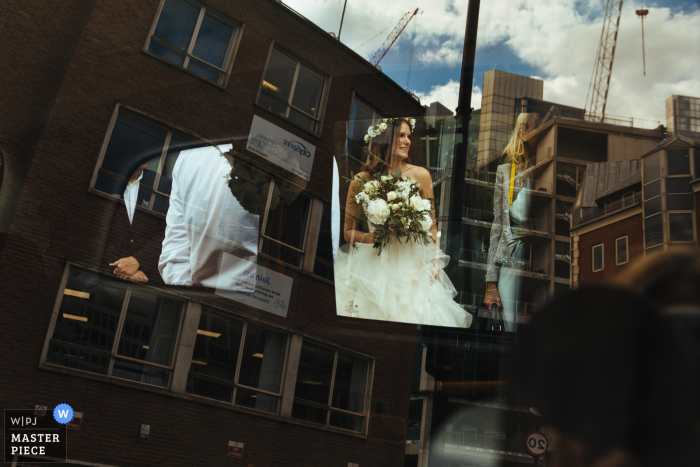 Vivo Islington Wedding Photography showing the Bride as she gets in wedding car as viewed through the window