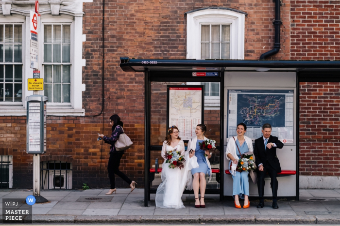 The Bride with her bridal party wait for a bus to take them to the ceremony at the Royal Hospital Chelsea