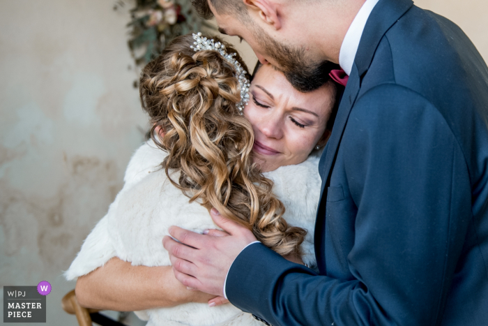 Oise wedding photographer created this image of the bride and groom hugging their daughter at the ceremony