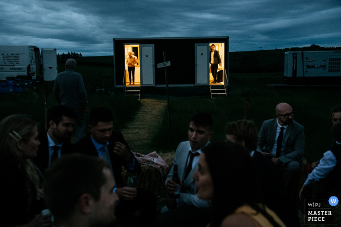 Farm wedding photography near Gifford - Night image of Guests standing in front of the toilets