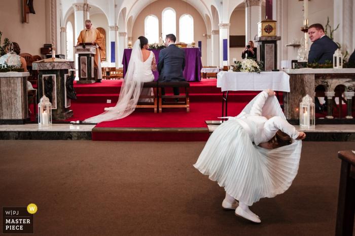 Salthill Galway Wedding Photo montrant la fille Page jouant dans l'église pendant la cérémonie