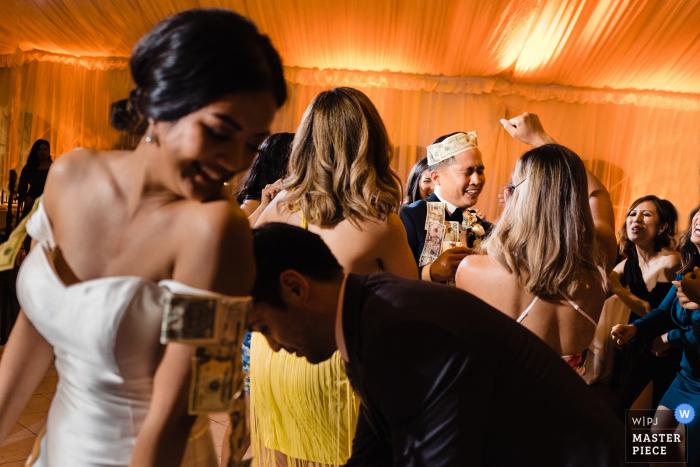 Fotografía de bodas en Coronado Marriot, San Diego, California - La novia y el novio se divierten con sus invitados durante el baile del dinero