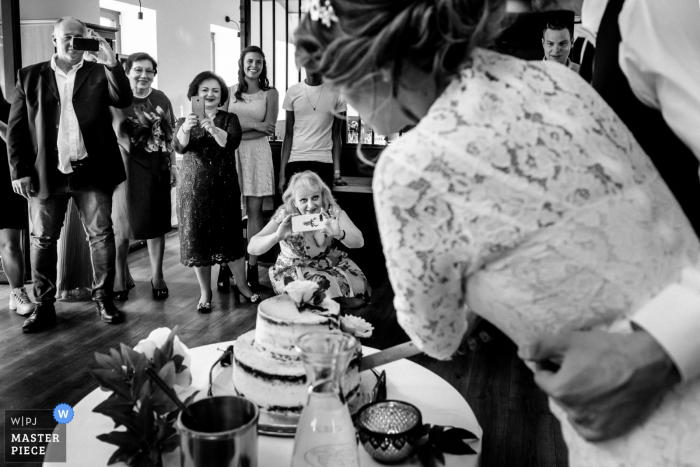A woman takes a picture with her phone as the bride and groom cut their cake in this black and white photo created by a Prague documentary wedding photographer.