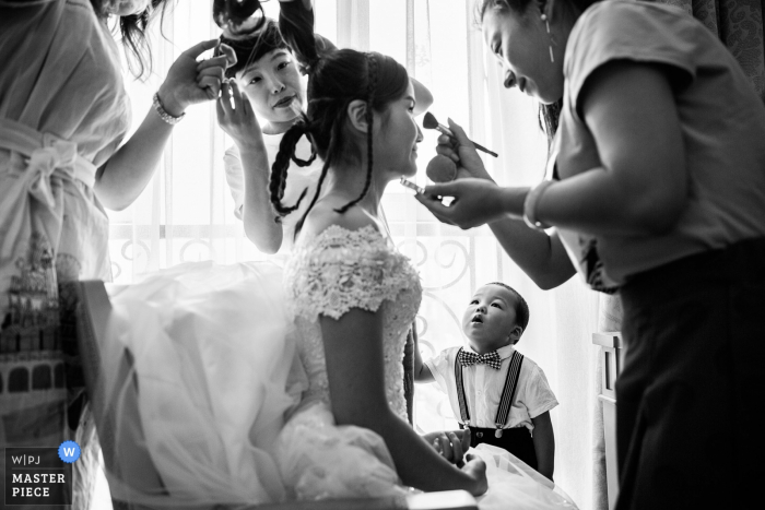 Bridesmaids and a little boy watch as the bride gets her makeup done in this black and white photo by a Beijing, China wedding photographer.