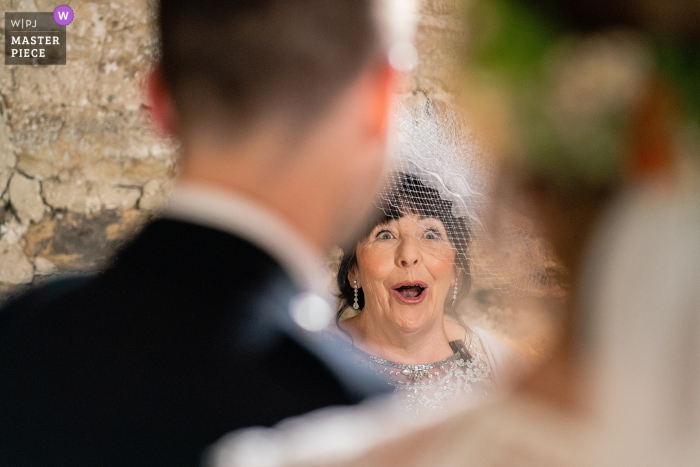 Mother of the Bride as seen between the heads of Bride and Groom as she reads out her ceremony speech at the Healey Barn, Northumberland