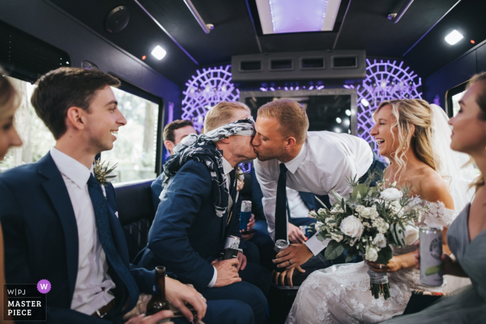 A man kisses the groom while he is blindfolded in this award-winning wedding photo captured by a Cleveland, OH documentary photographer.