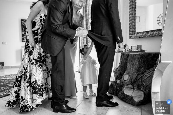 Ein Trauzeuge hilft einem anderen Mann, sich fertig zu machen, während ein kleines Mädchen versucht, auch auf diesem Foto zu helfen, das von einem Hochzeitsfotografen aus Sizilien im Castello Xirumi di Serravalle aufgenommen wurde.