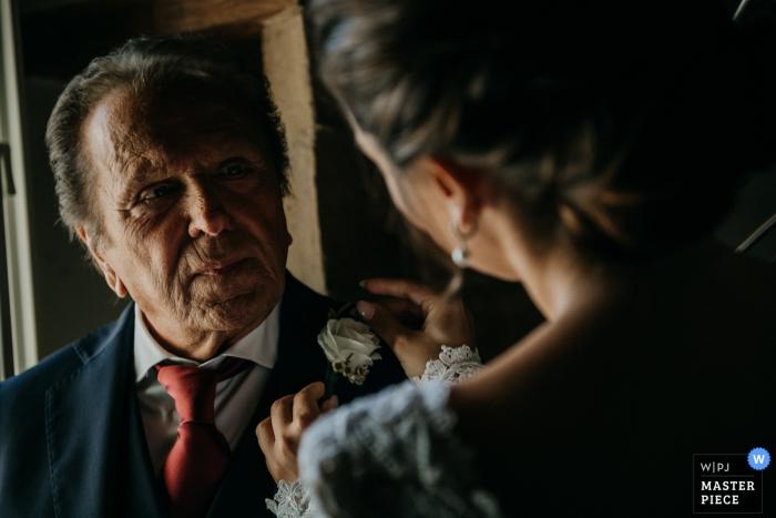 Castello di Montignano Hochzeitsfoto zeigt die Emotion des Vaters mit seiner Tochter, der Braut, als sie seine Blume auf seinen Mantel steckt