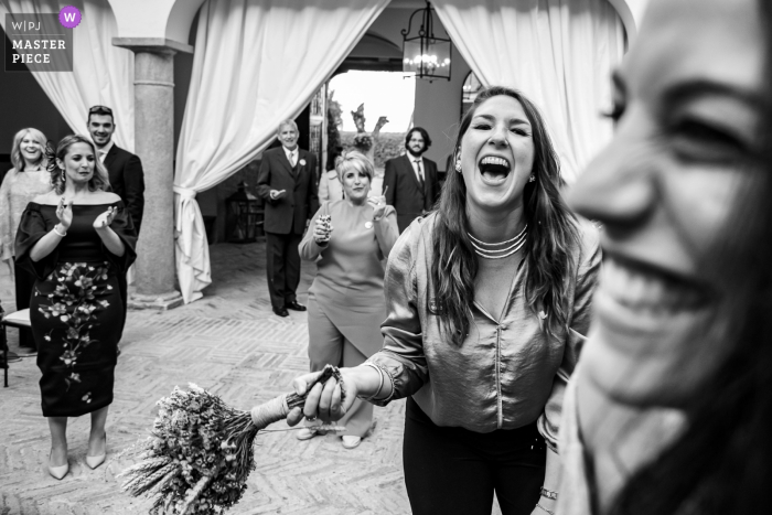 Palacio de Aldovea | Bridal bouquet throwing photograph at the wedding reception