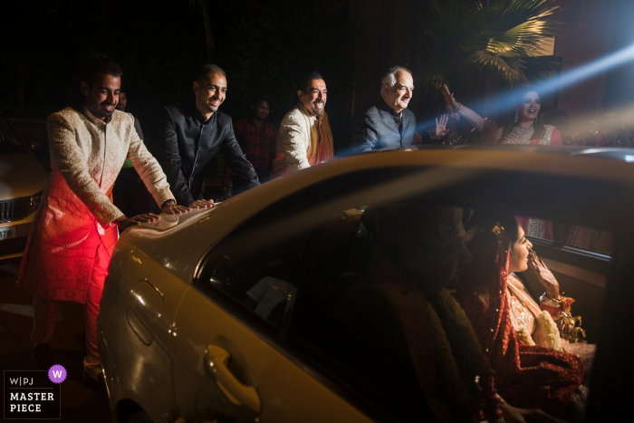 Guests push the bride and groom's vehicle as they say goodbye in this award-winning image captured by a Mumbai wedding photographer.