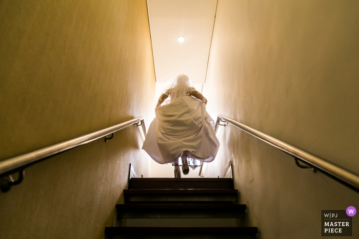 The bride walks up a flight of stairs into the light in Caracas in this image created by a documentary-style Venezuela wedding photographer.