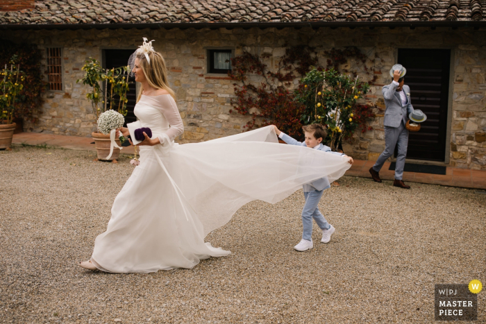 Castello di Spaltenna, Tuscany   Wedding Photo showing young son helping his mother with her dress