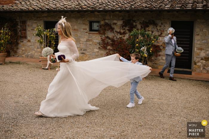 Castello di Spaltenna, Toskana | Hochzeits-Foto, das den jungen Sohn hilft seiner Mutter mit ihrem Kleid zeigt
