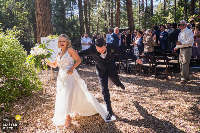 Rainbow Inn On Strawberry Creek, Idyllwild, California Wedding Photographer - The groom accidentally steps on the bride's dress as they exit the ceremony.