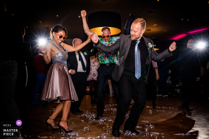 Guests enjoy dancing on the dance floor during the reception in this image captured by an Overijssel, Netherlands wedding photographer.
