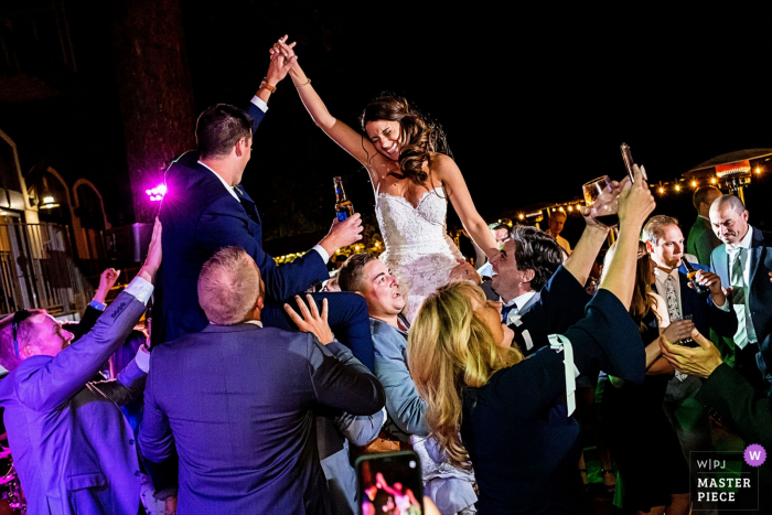 West Shore Cafe Lake Tahoe Wedding Photos - Bride and Groom are lifted up in celebration