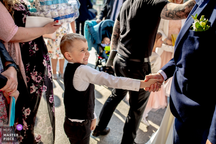 A boy gives a man a strong handshake after the ceremony at Parish of Bl. Władysława in Warsaw in this wedding photo created by a Lodz documentary photographer.