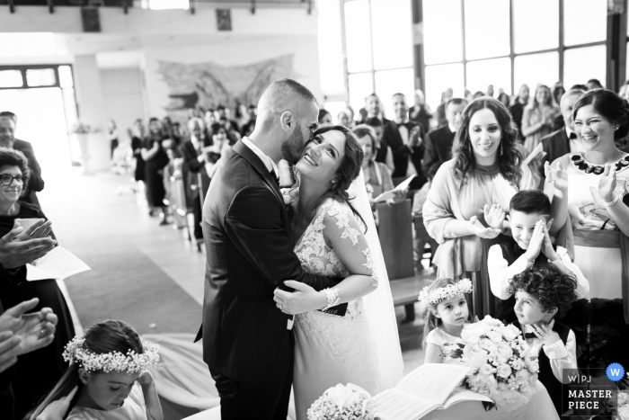 Guests watch as the groom kisses the bride on the cheek in Gioia Tauro in this black and white award-winning photo by a Calabria wedding photographer.