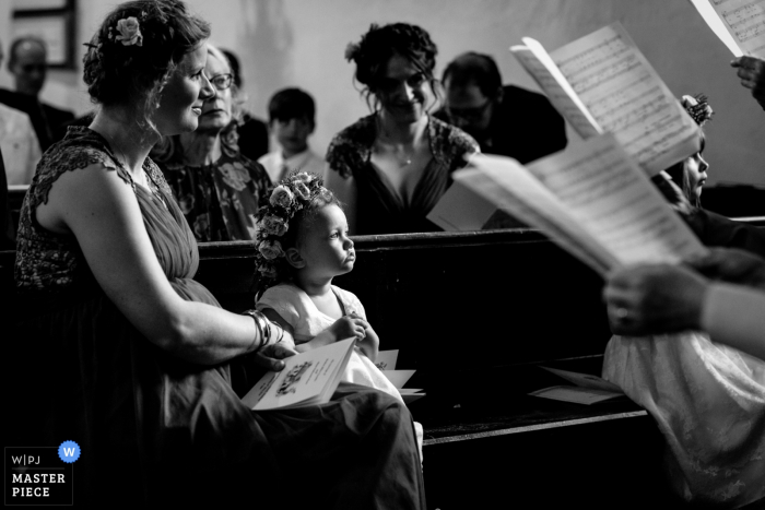 Wedding Photo from Petham Church, Petham, Kent, UK - A flower girl is mesmerized by the choir singing