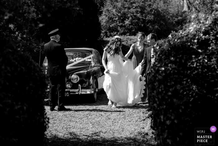 Hayne House, Kent, UK Wedding Photography | The bride arrives in windy conditions as her father and bridesmaid help with her dress