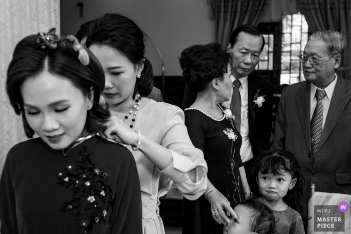 Die Familie hat einen schönen Moment zusammen, als sie sich auf die Zeremonie in Tay Ninh in diesem schwarz-weißen Hochzeitsfoto vorbereiten, das von einem Fotografen aus Ho Chi Minh, Vietnam, verfasst wurde.