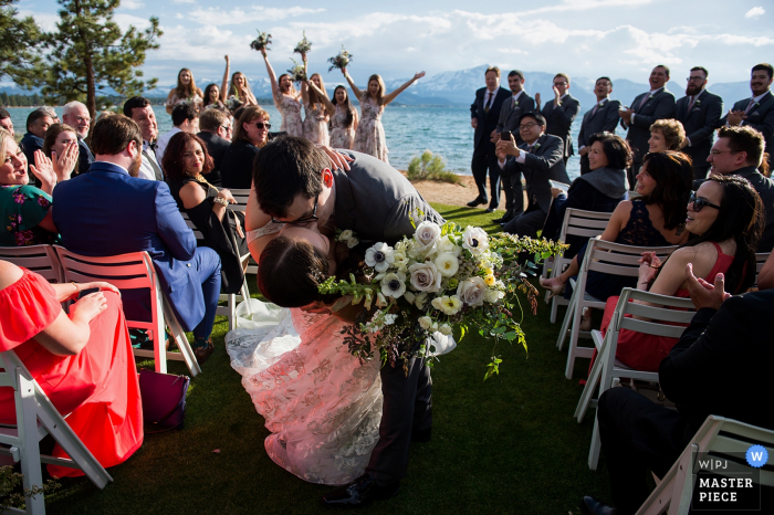 Weddings Outdoors at Edgewood, Lake Tahoe, NV | The groom surprises the bride by dipping her and kissing her as they leave the wedding ceremony.