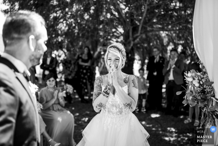 The bride brings her hands up to her face when she sees her groom waiting for her at their ceremony at Villa le Due Torrette Erbailla in this black and white image captured by a Lombardy wedding photographer. s