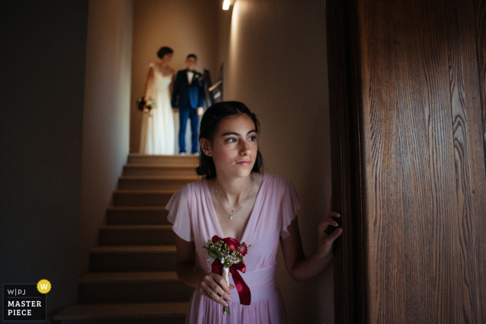 Reggio Calabria-Villa Tramontana Wedding Photographer | The bridesmaid looks timidly out before entering the scene
