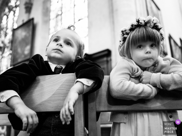 A young boy and girl lean over the backs of their chairs in this black and white wedding photo composed by a documentary-style Antwerpen, Flanders photographer.